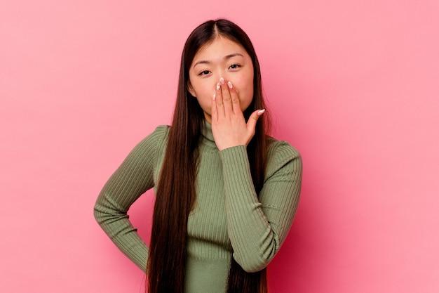 Giovane donna cinese isolata su sfondo rosa scioccata, coprendosi la bocca con le mani, ansiosa di scoprire qualcosa di nuovo. Foto Premium