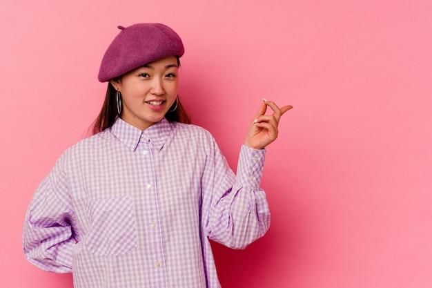 Giovane donna cinese isolata su sfondo rosa sorridendo allegramente indicando con l'indice di distanza.