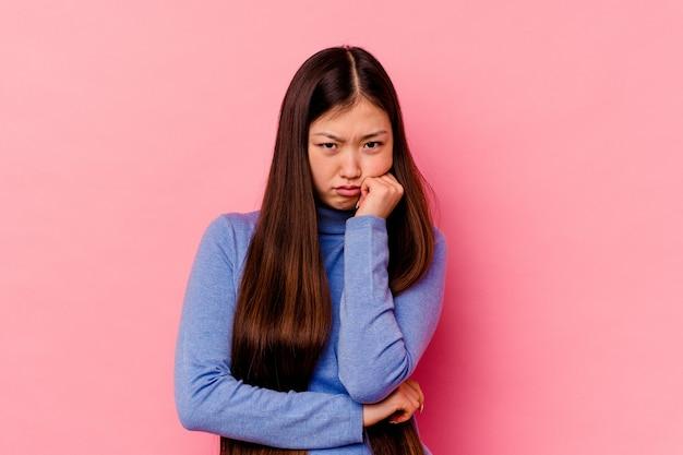 Giovane donna cinese isolata su sfondo rosa stanca di un compito ripetitivo.