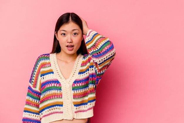 Giovane donna cinese isolata su sfondo rosa, toccando la parte posteriore della testa, pensando e facendo una scelta.