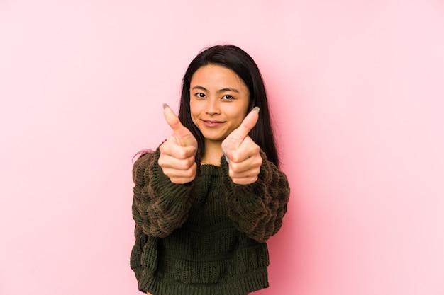 Giovane donna cinese isolata su uno sfondo rosa con il pollice in alto, applausi per qualcosa, il sostegno e il concetto di rispetto.