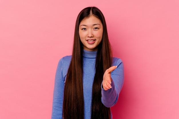 Giovane donna cinese isolata sul rosa che allunga la mano nel gesto di saluto.