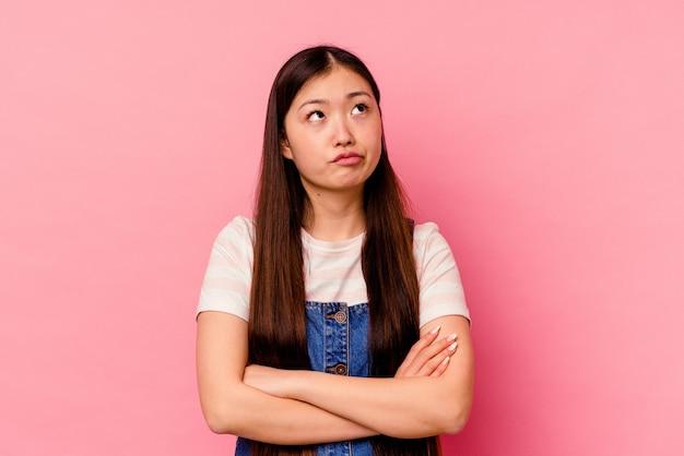 Giovane donna cinese isolata sul rosa stanca di un compito ripetitivo.