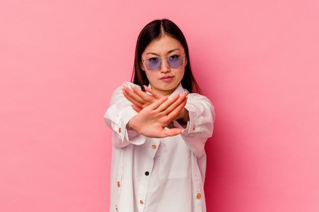 Giovane donna cinese isolata sulla parete rosa che fa un gesto di diniego