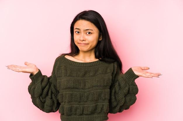 Giovane donna cinese isolata su una parete rosa dubitando e alzando le spalle nel gesto interrogativo.