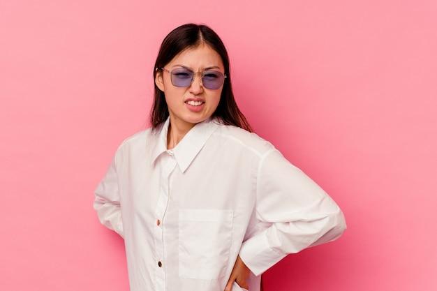 Giovane donna cinese isolata sulla parete rosa che soffre di mal di schiena.