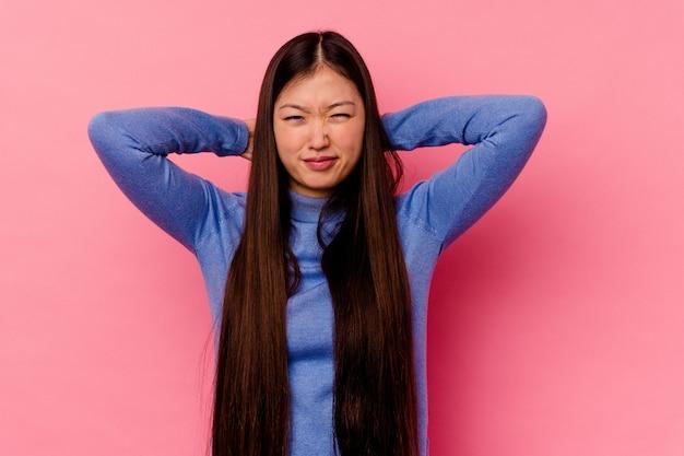 Giovane donna cinese isolata sulla parete rosa che soffre di dolore al collo a causa di uno stile di vita sedentario.