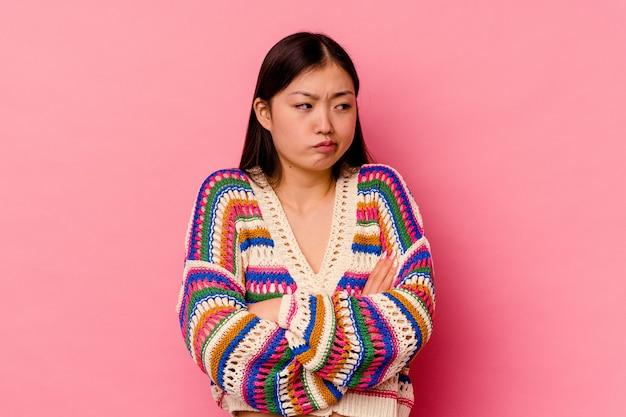 Giovane donna cinese isolata sulla parete rosa stanca di un compito ripetitivo