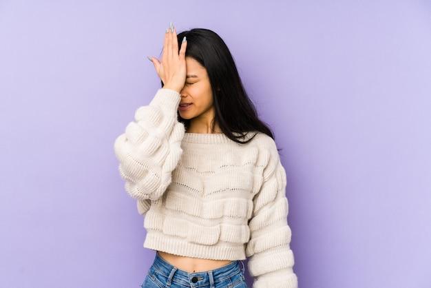 Giovane donna cinese isolata su uno spazio viola dimenticando qualcosa, schiaffeggiando la fronte con il palmo e chiudendo gli occhi.