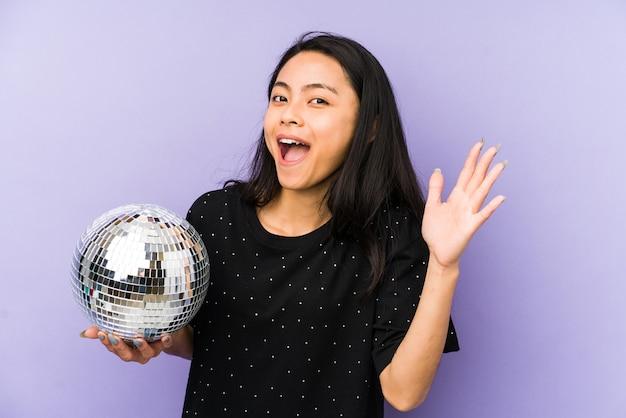Giovane donna cinese isolata su un muro viola allegro che tiene una palla da discoteca