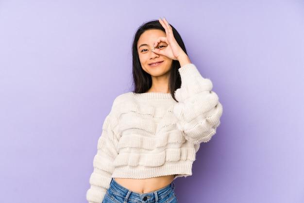 La giovane donna cinese isolata su una parete viola ha eccitato mantenendo il gesto giusto sull'occhio