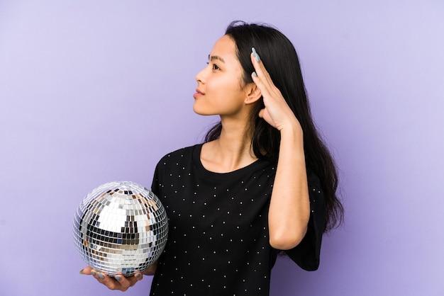 Giovane donna cinese isolata su una parete viola che guarda a un lato che tiene una palla da discoteca