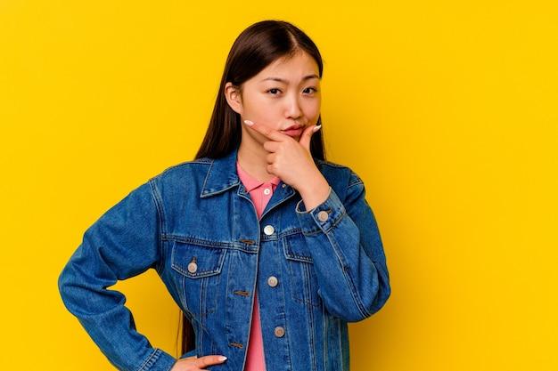 Giovane donna cinese isolata su sfondo giallo contemplando, pianificando una strategia, pensando al modo di fare affari.