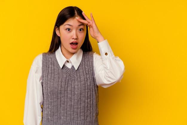 La giovane donna cinese isolata su sfondo giallo grida forte, tiene gli occhi aperti e le mani tese.