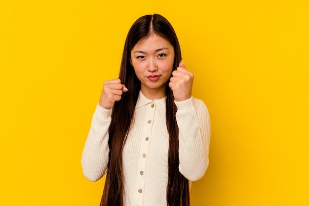 Giovane donna cinese isolata su sfondo giallo che mostra il pugno alla telecamera, espressione facciale aggressiva.