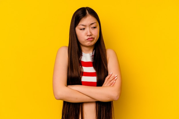 Giovane donna cinese isolata su sfondo giallo stanca di un compito ripetitivo.