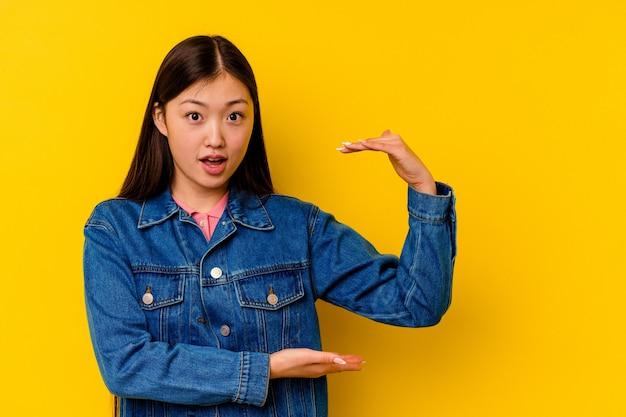 Giovane donna cinese isolata su giallo scioccato e stupito in possesso di uno spazio di copia tra le mani.
