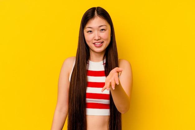 Giovane donna cinese isolata sul giallo che allunga la mano nel gesto di saluto.