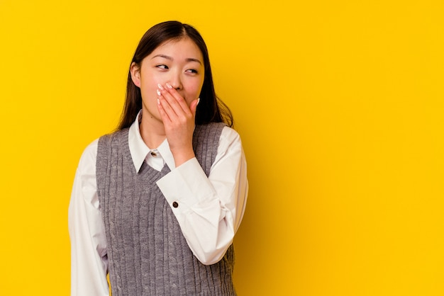 Giovane donna cinese isolata sul giallo premuroso che guarda a uno spazio della copia che copre la bocca con la mano.