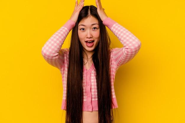 Giovane donna cinese isolata sulla parete gialla che grida, molto eccitata, appassionata, soddisfatta di qualcosa