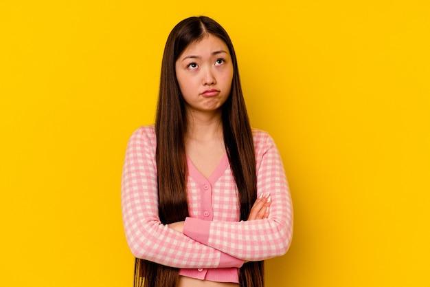 Giovane donna cinese isolata sulla parete gialla stanca di un compito ripetitivo.