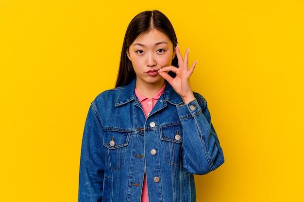 Giovane donna cinese isolata sulla parete gialla con le dita sulle labbra mantenendo un segreto
