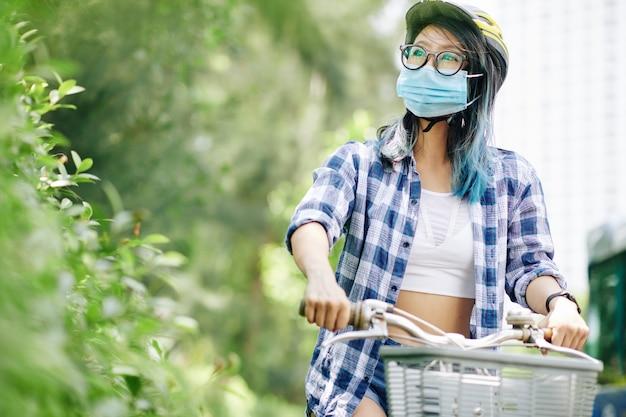 Giovane donna cinese nella mascherina medica che guida sulla bicicletta nel parco cittadino