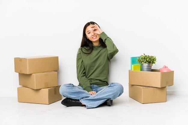 Giovane donna cinese che si trasferisce in una nuova casa eccitata mantenendo il gesto giusto sull'occhio.