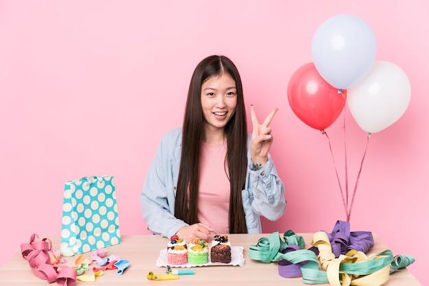 Giovane donna cinese che organizza un compleanno isolato che mostra il numero due con le dita.