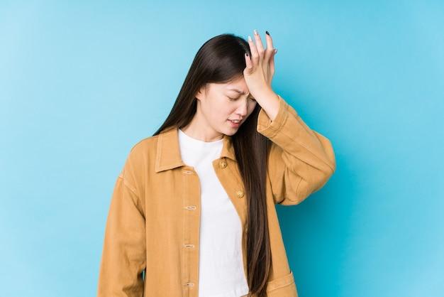Giovane donna cinese in posa in un blu dimenticando qualcosa, schiaffeggiando la fronte con il palmo e chiudendo gli occhi.