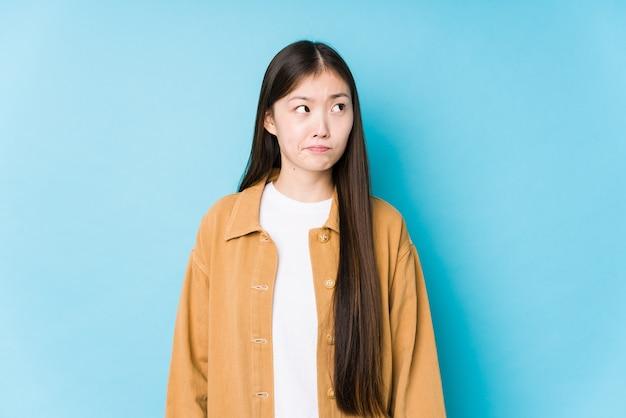 La giovane donna cinese che posa sull'azzurro isolato confusa, si sente dubbiosa e insicura.