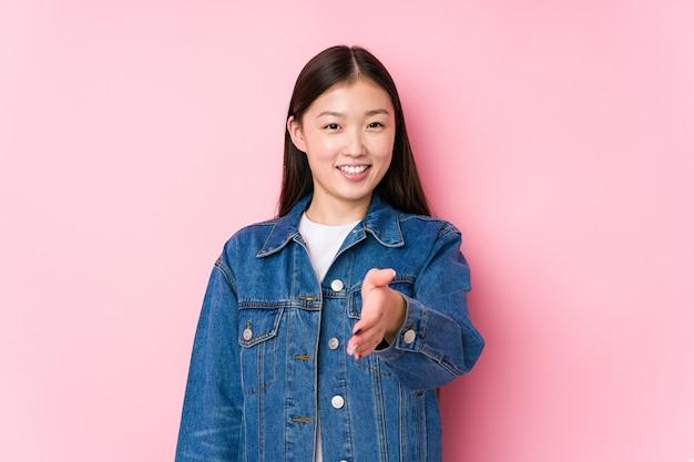 Giovane donna cinese in posa in uno sfondo rosa isolato allungando la mano alla telecamera nel gesto di saluto.