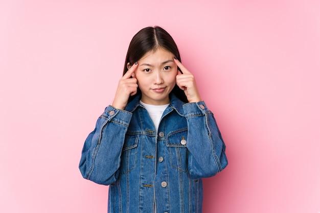 La giovane donna cinese che posa in una superficie rosa isolata si è concentrata su un compito, mantenendo gli indici che puntano la testa.