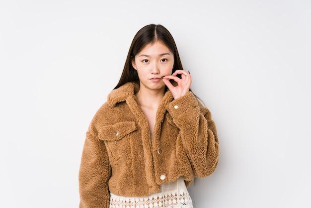 Giovane donna cinese in posa in un muro bianco isolato con le dita sulle labbra mantenendo un segreto.