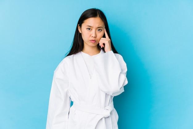 La giovane donna cinese che pratica il karatè ha isolato il tempio indicante con il dito, pensando, messo a fuoco su un compito.