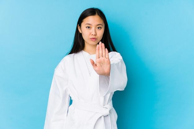 Karatè di pratica della giovane donna cinese isolato in piedi con la mano tesa mostrando il segnale di stop, impedendoti.