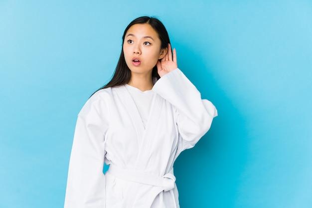 Karatè di pratica della giovane donna cinese isolato cercando di ascoltare un gossip.