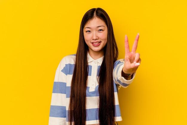 Giovane donna cinese che mostra il segno di vittoria e che sorride ampiamente.
