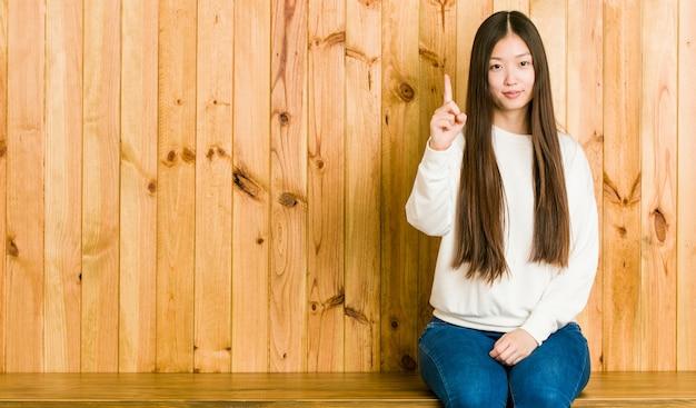 Giovane donna cinese che si siede su un posto di legno che mostra il numero uno con il dito.