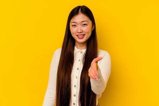 Giovane donna cinese che allunga la mano alla macchina fotografica nel gesto di saluto.