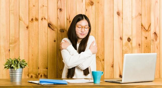 Giovane donna cinese che studia sui suoi abbracci da scrivania, sorridendo spensierata e felice.