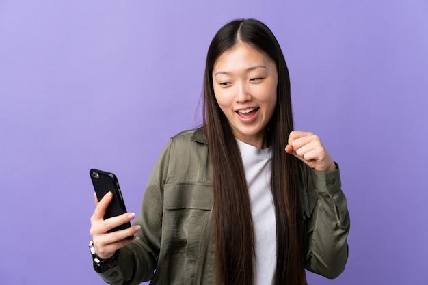Giovane donna cinese che per mezzo del telefono cellulare sopra la parete porpora isolata che celebra una vittoria