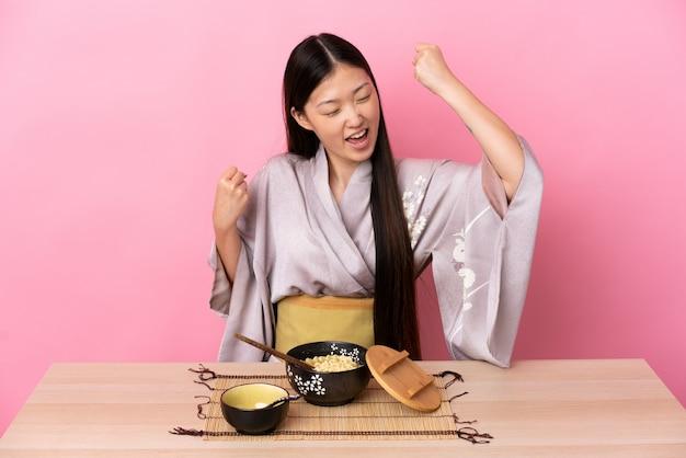 Kimono da portare della giovane donna cinese e mangiare le tagliatelle che celebrano una vittoria