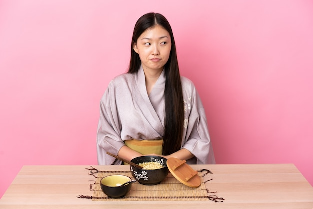 Kimono d'uso della giovane donna cinese e mangiare le tagliatelle che hanno dubbi mentre osservando in su