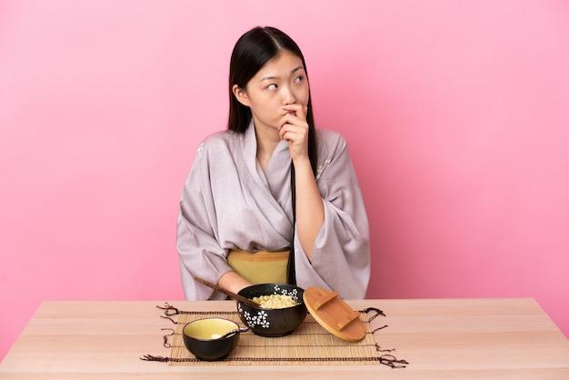 Kimono da portare della giovane donna cinese e mangiare le tagliatelle che hanno dubbi e con l'espressione confusa del fronte