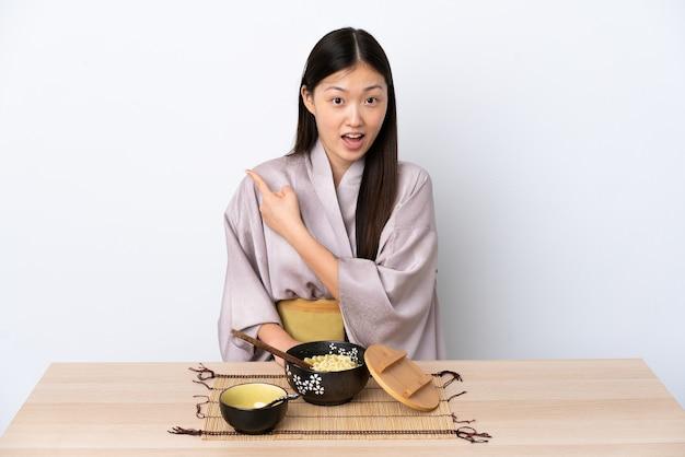 Kimono da portare della giovane donna cinese e mangiare le tagliatelle sorpreso e indicando lato