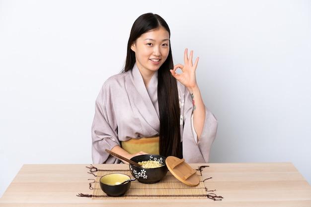 Kimono da portare della giovane donna cinese e mangiare le tagliatelle
