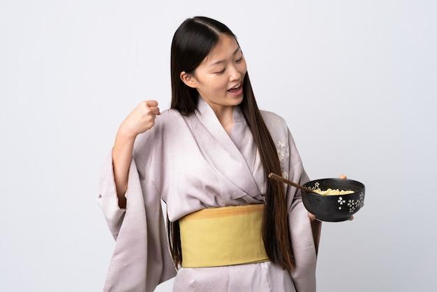 Kimono d'uso della giovane donna cinese sopra la parete bianca isolata che celebra una vittoria mentre tenendo una ciotola di tagliatelle con le bacchette