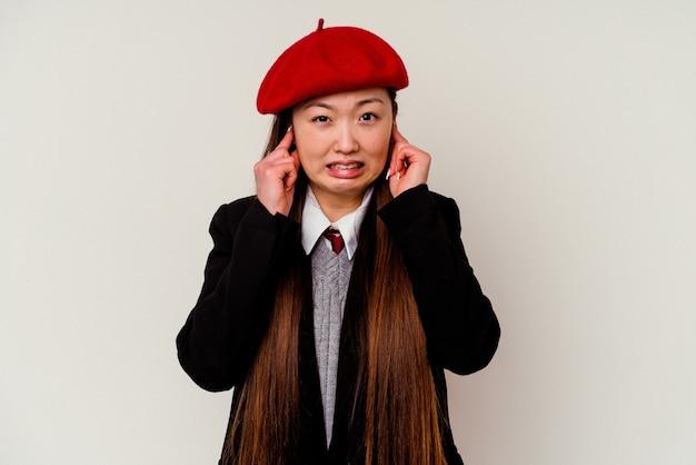 Giovane donna cinese che indossa un'uniforme scolastica isolata sulle orecchie bianche della copertura con le mani.