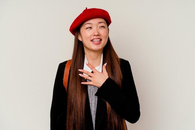 La giovane donna cinese che indossa un'uniforme scolastica isolata sul muro bianco ride ad alta voce mantenendo la mano sul petto.
